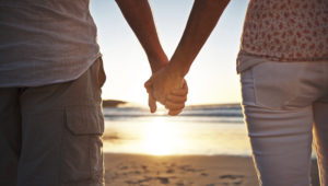 Cropped view of a senior couple holding hands